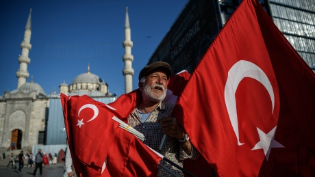 A man sells Turkish national flags near the new mosque in the Eminonu district in Istanbul, on June 9, 2016. Turkey has suffered a spate of bombings this year, including two suicide attacks in tourist areas of Istanbul and two car bombings in the capital Ankara effected tourism industry in Turkey reported by Turkish media. / AFP / OZAN KOSE        (Photo credit should read OZAN KOSE/AFP/Getty Images)