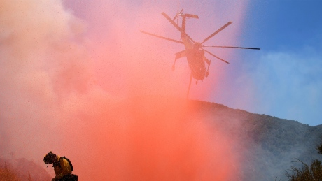 A fire fighter is sprayed with retardant as a helicopter makes a drop in the Angeles National Forest near Los Angeles Monday, July 25, 2016.