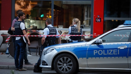 Police stand at the scene of where a 21-year-old Syrian refugee killed a woman with a machete and injured two other people in the city of Reutlingen, Germany on July 24, 2016.