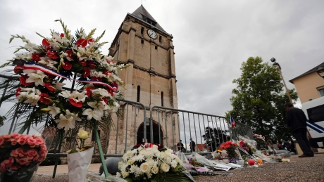A wreath of flowers from Muslim of France Associations is placed with flowers next to the church where an hostage taking left a priest dead the day before in Saint-Etienne-du-Rouvray, in Normandy on Wednesday.