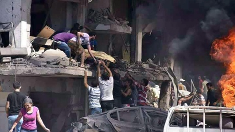 In this photo released by the Syrian official news agency SANA, Syrians carry the body of a victim from a building damaged in twin bombings struck Kurdish town of Qamishli, Syria, Wednesday, July 27, 2016. Bombings struck a crowd in a predominantly Kurdish town in northern Syria on Wednesday, killing 44 people and wounding dozens more, Syria's state-run news agency and Kurdish media reported.