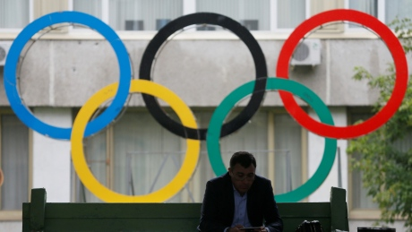 A man uses his tablet computer as he sits near Olympic rings placed in the courtyard of the Russian Olympic Committee headquarters in Moscow, Russia, July 22, 2016.  REUTERS/Maxim Shemetov - RTSJ8WT
