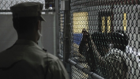 A Sailor assigned to the Navy Expeditionary Guard Battalion stands watch over detainees in a cell block in Camp 6 at Guantanamo Bay naval base in a March 30, 2010 file photo provided by the US Navy. President Barack Obama urged lawmakers on Tuesday to give his plan to close the U.S. military prison at Guantanamo Bay, Cuba, a