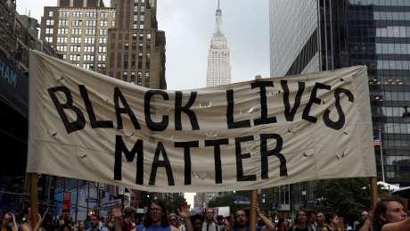 People take part in a protest against the killings of Alton Sterling and Philando Castile during a march through Manhattan, with the Empire State Building seen in the background, in New York July 7, 2016. REUTERS/Darren Ornitz - RTX2K9J3